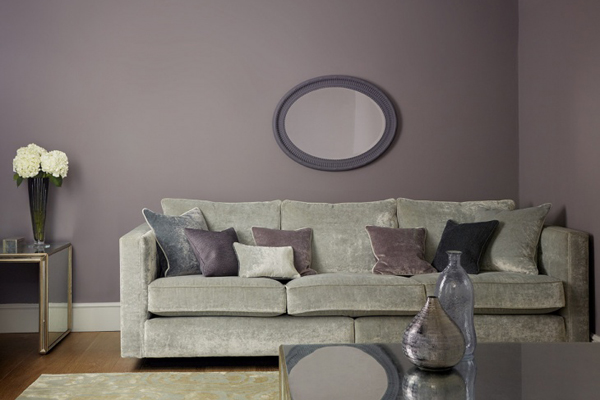 Mauve painted wall with velvet sofa