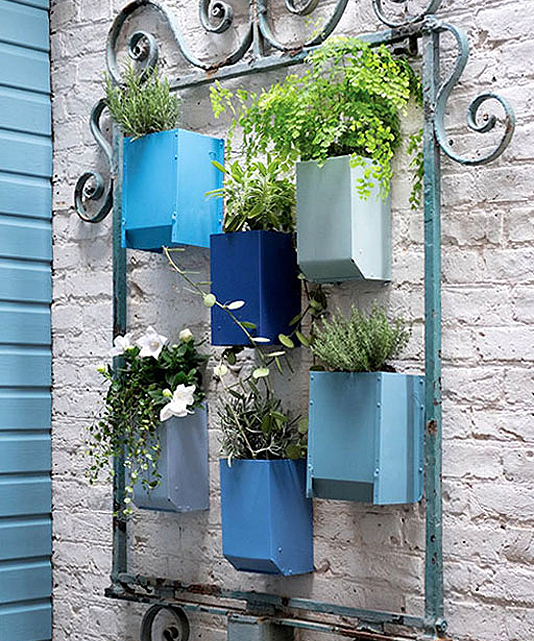 Wall with mounted plant pots in shades of blue
