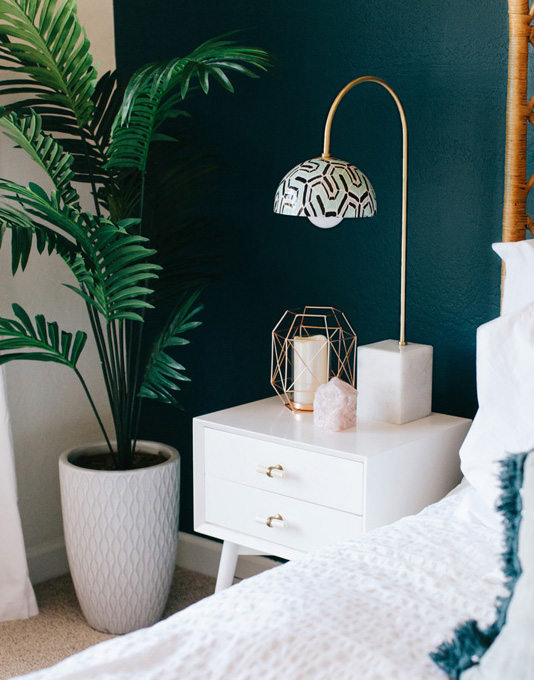 Teal wall with bedside table and accessories