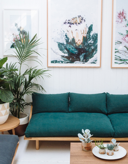 Teal sofa with abstract floral artwork